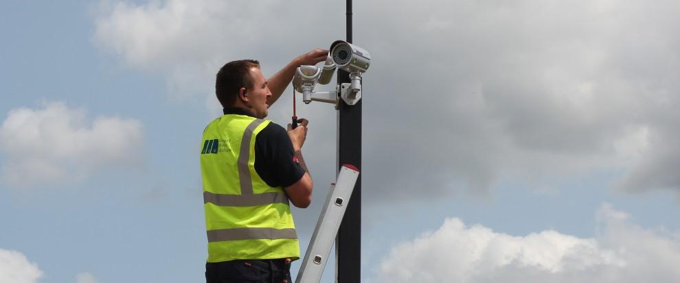 Engineer installation cctv system on ladder - Project Skills Solutions