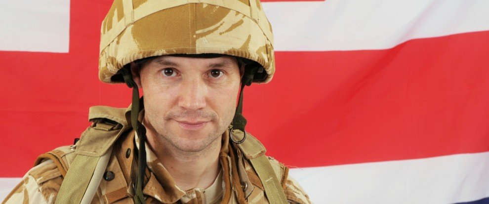 Military soldier standing in front of British flag