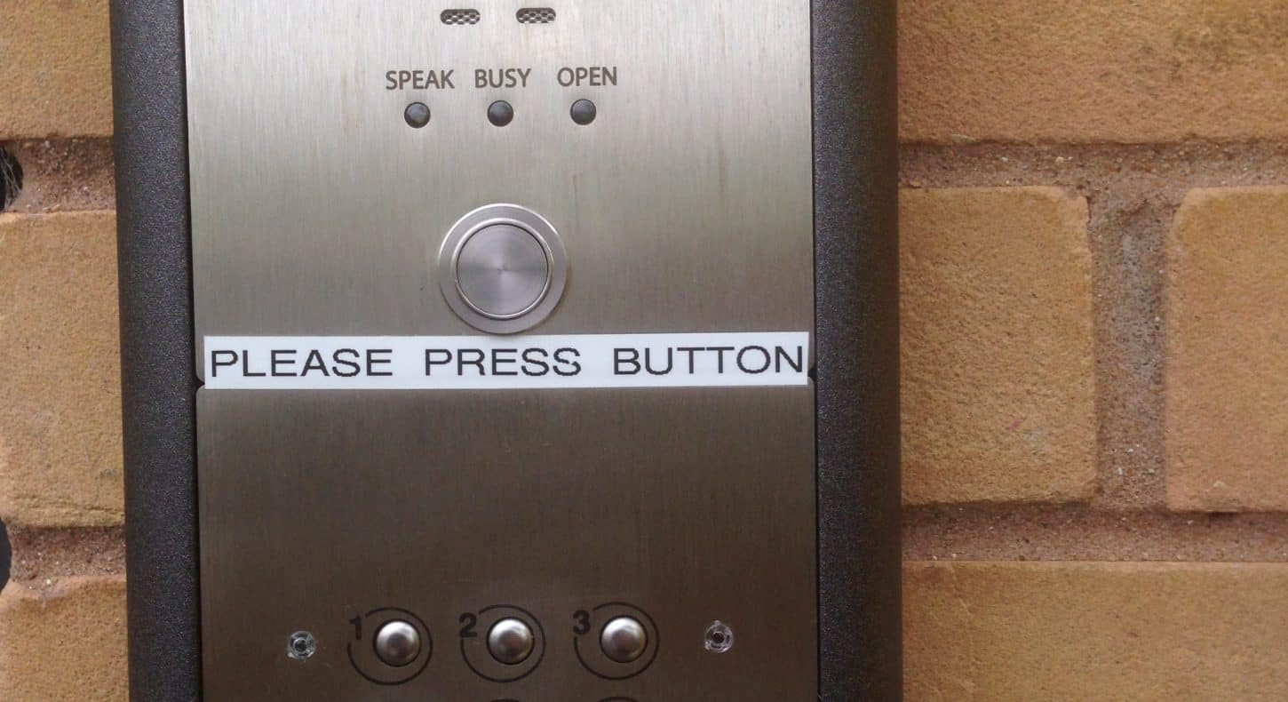Access control keypad equipment on brick wall.